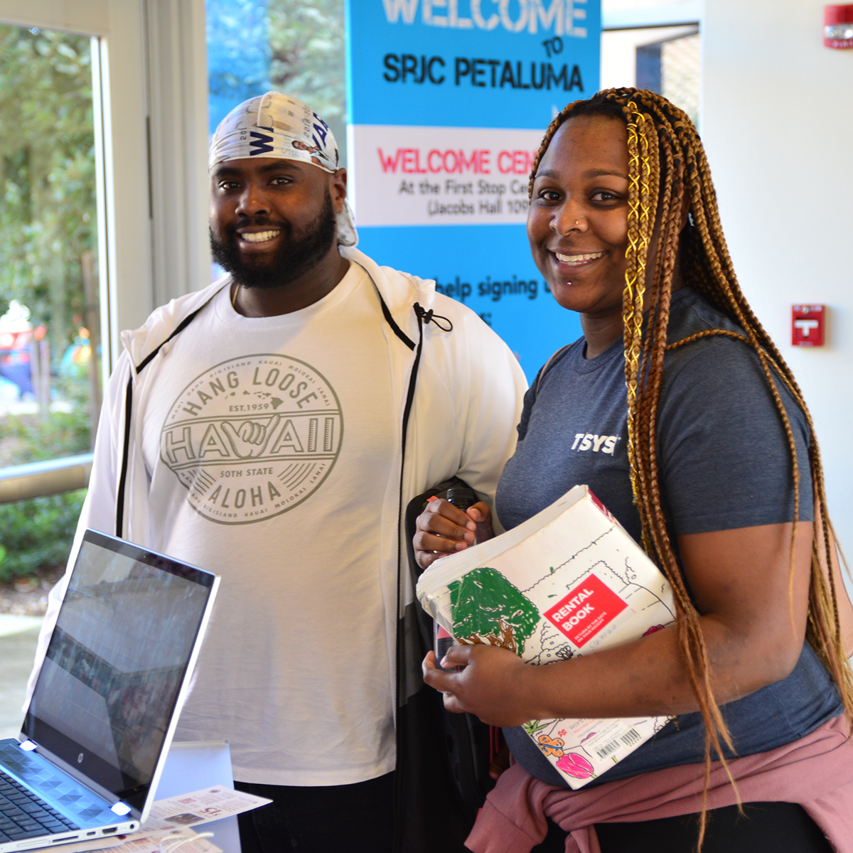 Two students in front of a sign that says welcome to srjc Petaluma